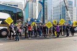 HARVEY CASTRO/STUDIO369 PHOTOGRAPHY - Protesters blockade a tech coach in downtown San Francisco.