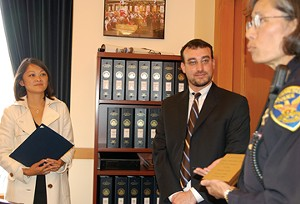 Rabbi Joshua Strulowitz of San Francisco's Orthodox Adath Israel watches as Supervisor Carmen Chu and Police Chief Heather Fong sign papers granting Jews the right to carry objects on the Sabbath. The chances are exactly 100 percent neither Chu nor Fong ever thought they'd be called upon to do this. - STACEY PALEVSKY