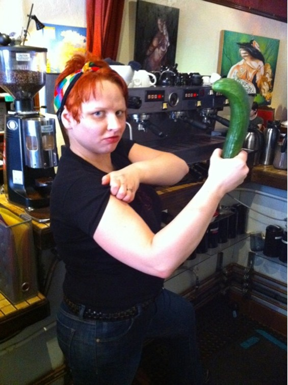 """Rose White holds a """"g-spot cucumber"""" in the """"We Can Do It!"""" pose."""