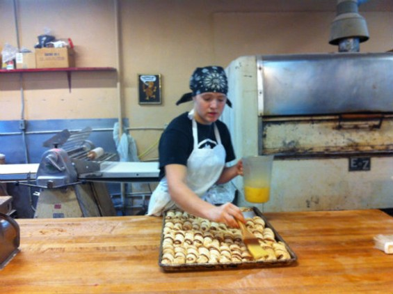 Rowan, Nabalom employee, egg washes the bakery's famous cinnamon twists - MOLLY GORE