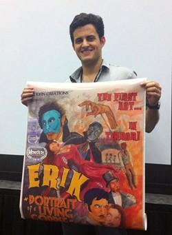 Ryan Bijan proudly displays a poster for Erik: Portrait of a Living Corpse - BROOK E. MANTIA