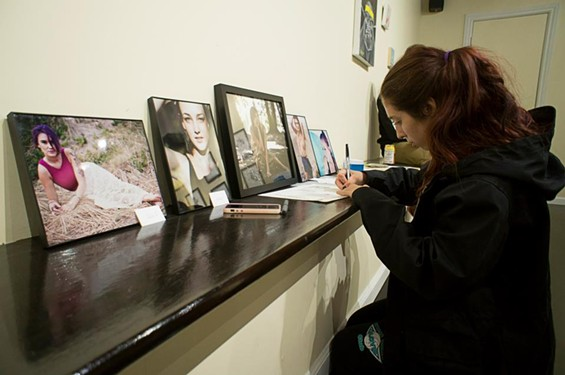 Sam Battles, featured photographer in the exhibit, carefully prepares her photographs to hang on Sunday.
