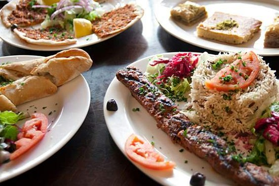 Savory pies, adana kebabs, and semolina cake from Grill House Mediterranean. - LARA HATA