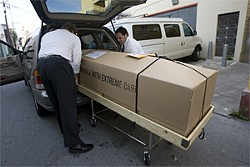PAUL TRAPANI - Staff at the funeral home load Lopez' casket for the trip to the airport.
