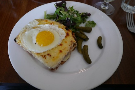 The Croque Madame, topped with a sunny-side up egg and served with cornichons
