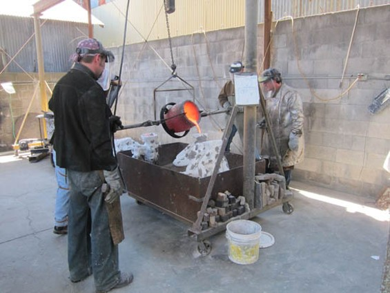 The pouring of the bronze. Some workers wear leather aprons, but the awesome silver coat is made of teflon.