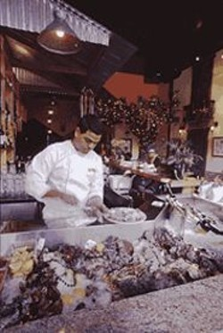 ANTHONY  PIDGEON - The World Is My ...: Oyster shucker Carlos Flores prepares a plate of - bivalves at Le Krewe's ice-packed oyster bar.