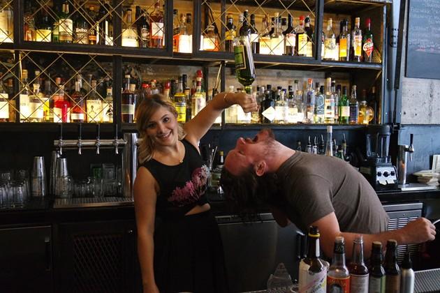 Julie feeds Howie Slater Chartreuse at Drexl Bar in Oakland - JULIE FIGUERAS