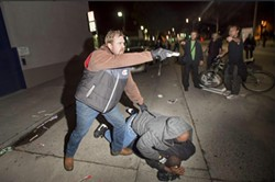 An undercover CHP officer brandishes a gun at protesters in Oakland, while his partner makes an arrest. - NOAH BERGER/REUTERS