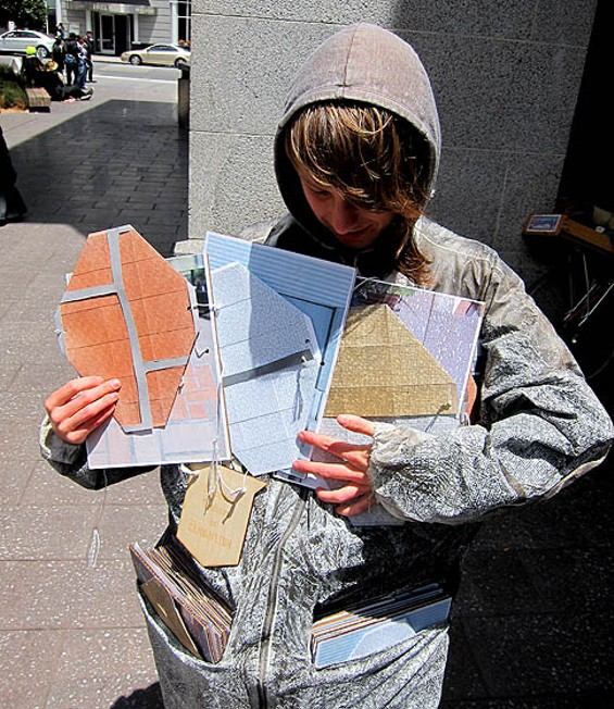 Veronica Graham demonstrates camouflage customized for invisibility against Market Street's sidewalk, the Ferry Building, and Mint Plaza. - LARISSA ARCHER