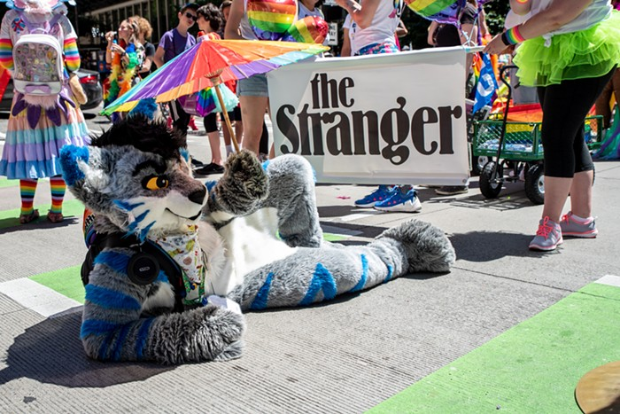 A local furry shades himself with a rainbow sunbrella while waiting for the parade to start. He came fully prepared with a portable fan, hydration pack, and a shade to keep from overheating.