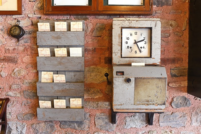 Old time clock at a work place together with time card holding shelves.