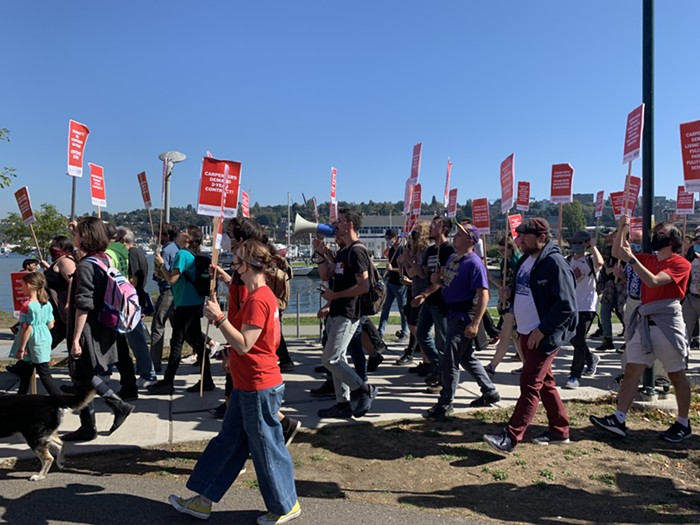 The solidarity rally marches to AGC with red signs that credit Sawant and PJM