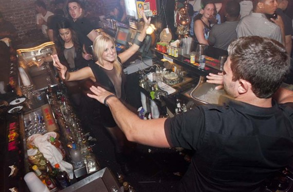 1:08 a.m. - Serving from a bar that wraps around them, bartenders (from upper left) Taylor Radkte, Talya Tacosa, Camille Kostin and Richie Masters start dancing during the Tini Temptress Cocktail Party at the Lucky Buddha.