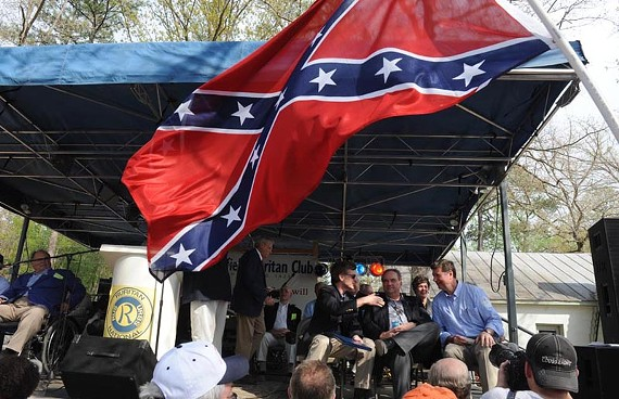 A Confederate flag flutters in the audience as Gov. Bob McDonnell, Lt. Gov. Bill Bolling and U.S. Senate candidate George Allen chat on stage at April's Shad Planking in Wakefield. - SCOTT ELMQUIST