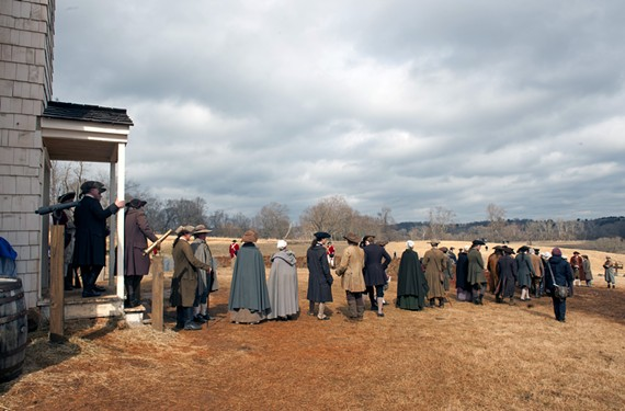 "A few hours after a downpour on a cold day in late February, a line of background actors prepares for a sweeping shot on the set of ""Turn,"" west of Richmond. Just over the hill to the right is the set for Setauket, which appears onscreen as a small, coastal town. - SCOTT ELMQUIST"