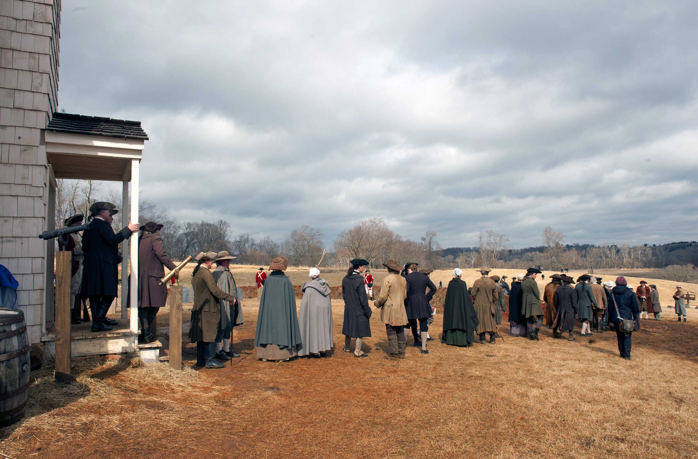 """A few hours after a downpour on a cold day in late February, a line of background actors prepares for a sweeping shot on the set of """"Turn,"""" west of Richmond. Just over the hill to the right is the set for Setauket, which appears onscreen as a small, coastal town. - SCOTT ELMQUIST"""