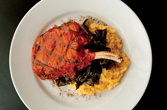 A pork chop brined in bourbon and sweet tea tops a base of cheese grits and greens at Mint New Casual Cuisine in the Fan. - SCOTT ELMQUIST