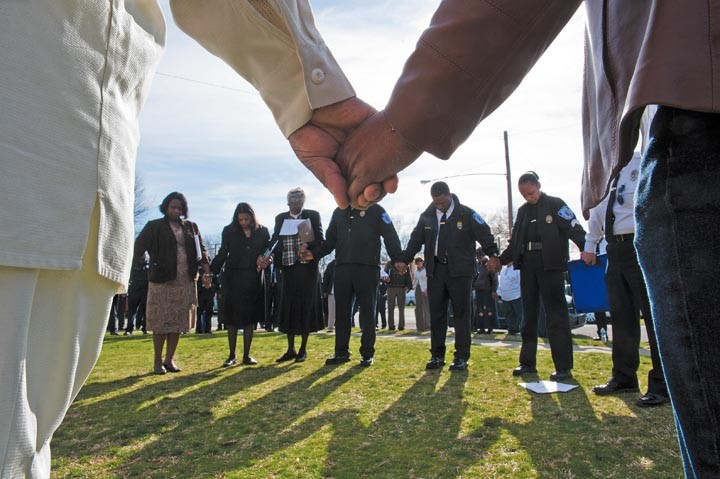 A prayer in the city: Police officials and local clergy bow their heads for peace at Hillside Court in South Richmond, the site of three recent homicides. - PHOTOS BY SCOTT ELMQUIST