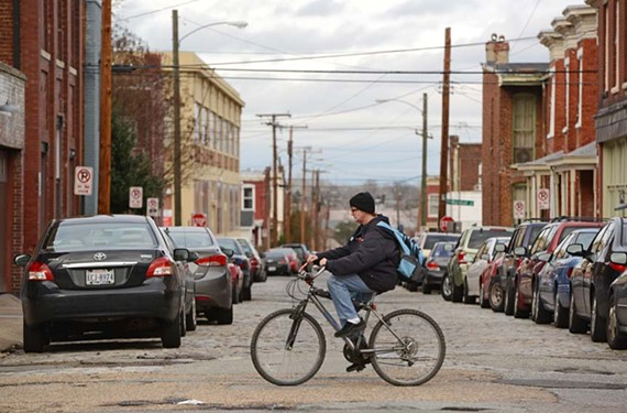 A proposal in the General Assembly would require motorists to check for cyclists, such as this one at Broad and Goshen streets, before opening doors into traffic. - SCOTT ELMQUIST