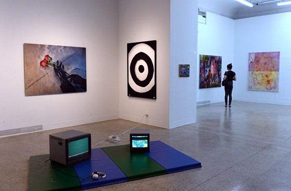 A visitor to the final Anderson Gallery installation examines a work by Lee Piechocki, a VCU painting and printmaking graduate student, whose additional works are shown nearby. The video and photography piece, foreground, is by graduate student Anthony Smith.