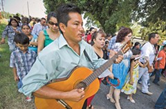 Accompanied by guitar and tambourine, the Mixtecos sing hymns while they walk around the quiet neighborhood in Manchester. - SCOTT ELMQUIST
