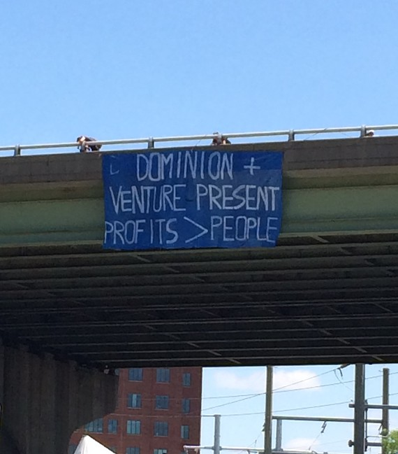 Activists unfurled signs criticizing Dominion and Venture Richmond during the busy second day of the annual Dominion Riverrock event at Brown's Island.
