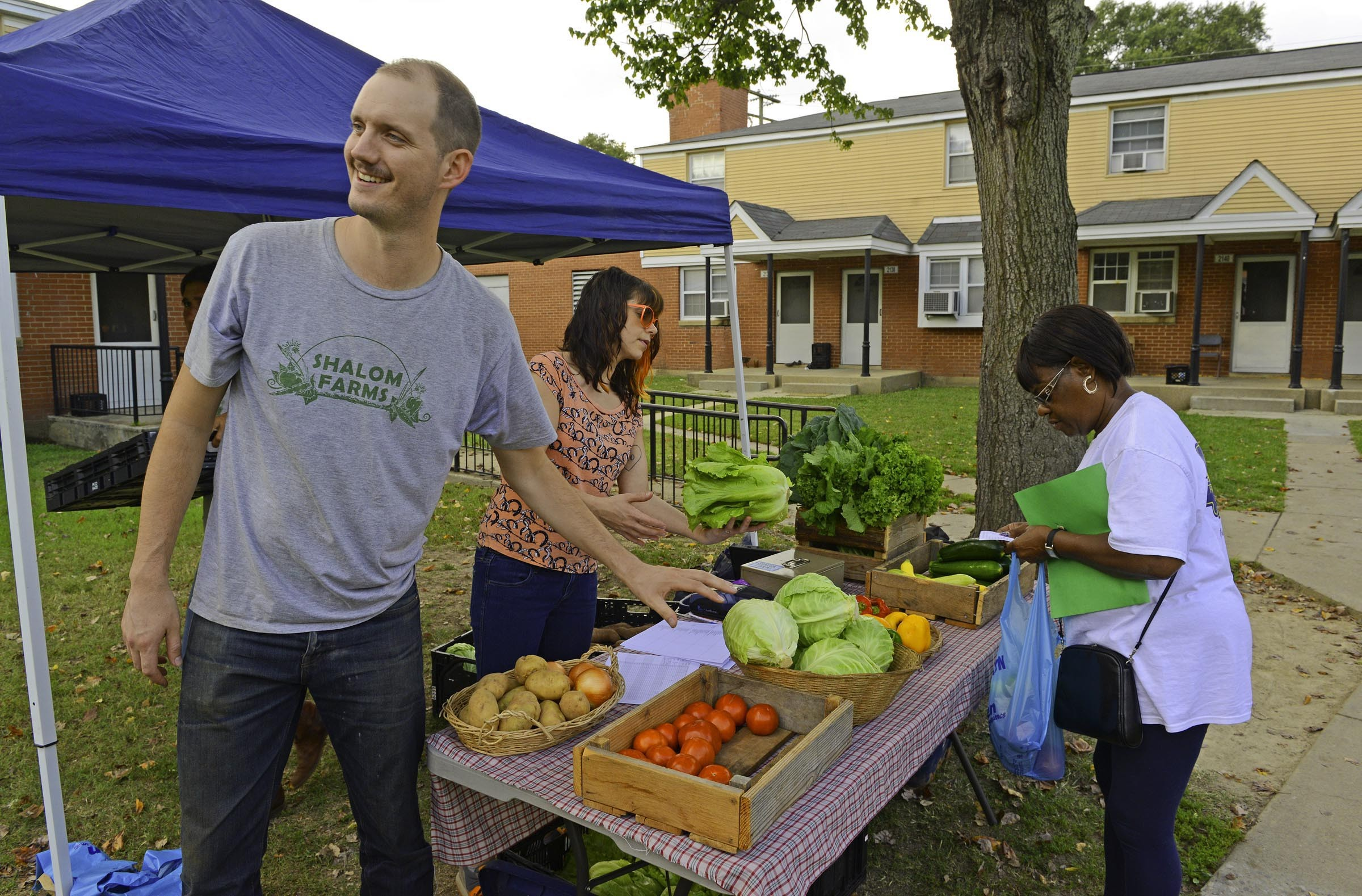 Among those tackling the challenge of getting fresh, healthy food into some Richmond neighborhoods is Dominic Barrett of Shalom Farms, at this stand in Creighton Court. - SCOTT ELMQUIST