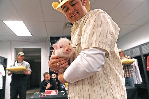 Anthony Oppermann, the Squirrels' media director, poses with Parker, the team's new rally pig.