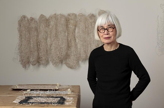 """Artist Kiyomi Iwata stands in front of work from her new retrospective, """"From Volume to Line,"""" currently running at the Visual Arts Center of Richmond."""