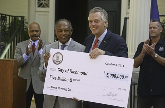At a press event in October 2014, Gov. Terry McAuliffe presents Mayor Dwight Jones a check for $5 million in state incentives that will go toward bringing Stone Brewing Co. to Richmond. - SCOTT ELMQUIST