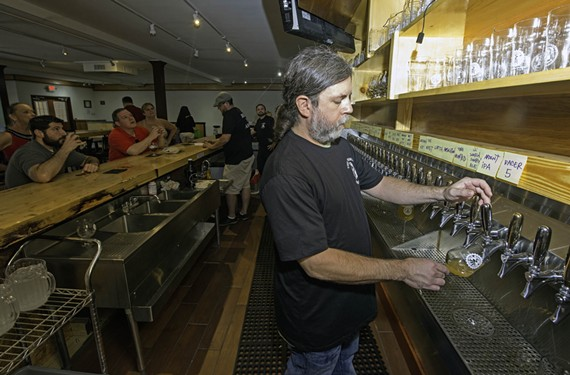 Bartender William Benn pours a Bear Republic Racer 5 IPA at the Answer, the new brewpub from Mekong owner An Bui. The bar can accommodate as many as 80 beers on tap.