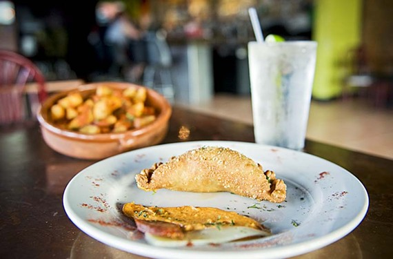 Beyond nachos: Try some bar food less ordinary, such as the homemade empanadas and patatas bravado at Emilio's Tapas Bar in the Fan. - ASH DANIEL