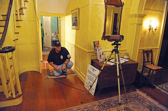 "Big Ray Rucker of Ghost Raps RIP sets up a camera in Hopewell's Weston Plantation. ""I always ask the client, 'What do you expect of us and what will you do with the information,'"" the ghost hunter says. - SCOTT ELMQUIST"