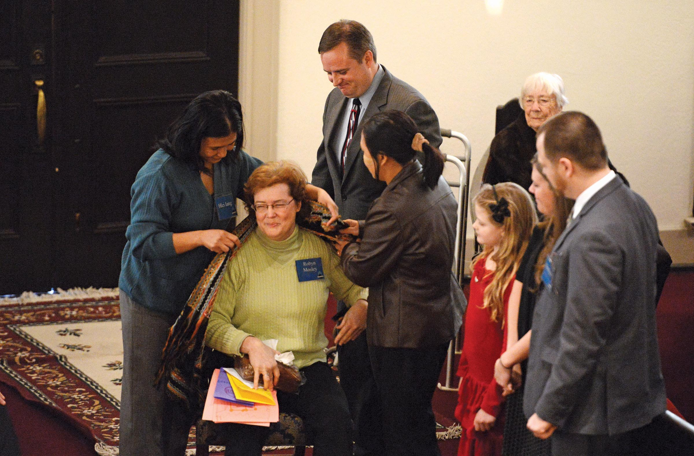 Burmese members of Tabernacle's congregation present a hand-woven shawl to Robyn Mosley on her last Sunday as a member of the church before she moves to Georgia.