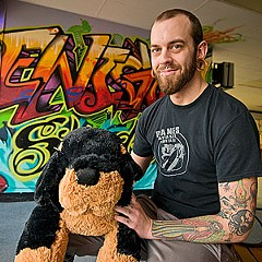 Cameron McConnell, a body piercer at Enigma Tattoo, holds a stuffed animal donated as part of the shop's Tats for Toys program.