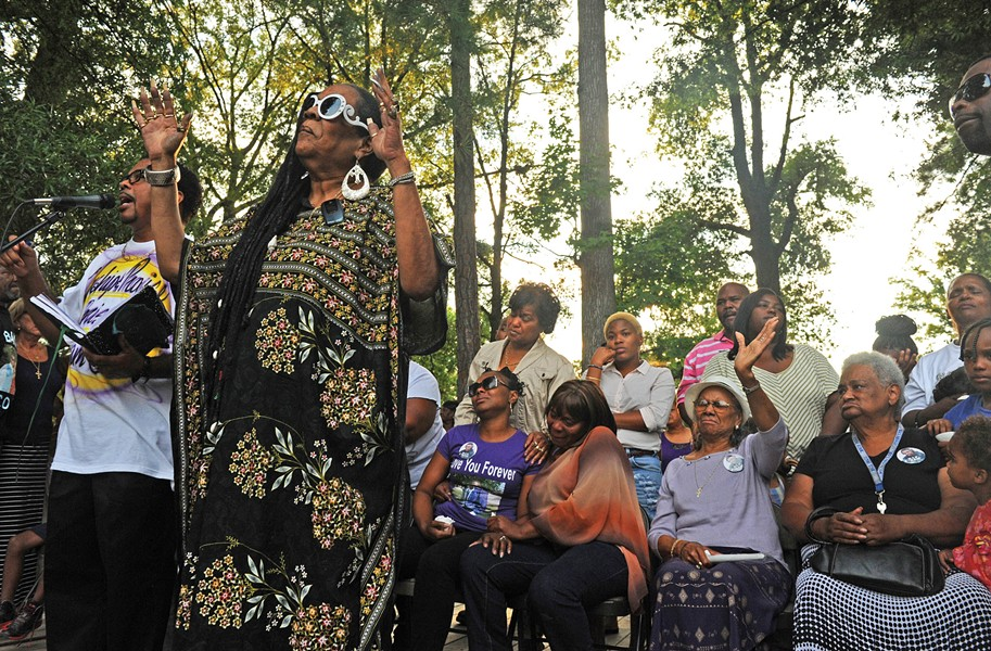 Citizens Against Crime founder Alicia Rasin addresses 300 people at a vigil last week for Zekei Johnson, 18, who was shot to death. His mother, Shankeithy Johnson, sits behind her. - SCOTT ELMQUIST