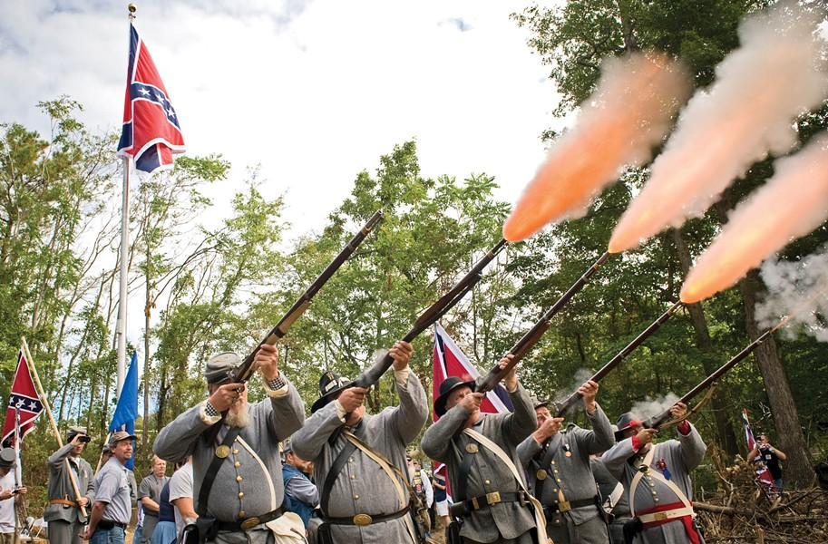 Civil War re-enactors fire a salute while the Virginia Flaggers raise the Confederate battle flag in Chester on Saturday. - ASH DANIEL