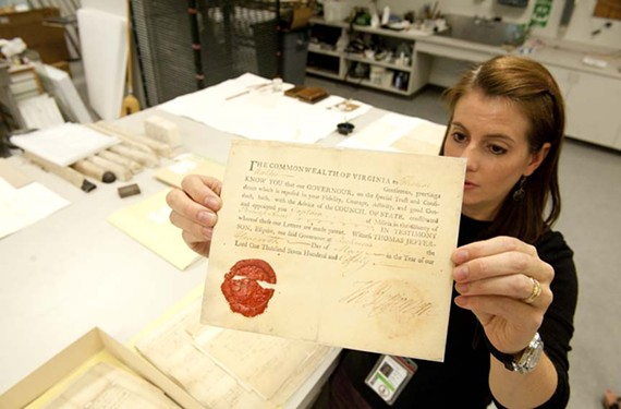 Conservator Leslie Courtois holds a resolution signed by Thomas Jefferson — one of the 2,500 documents she'll be working to restore. - SCOTT ELMQUIST