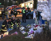 Firefighters kneel in front of a memorial along the road to Sandy Hook Elementary School, a day after the shooting in Newtown, Conn.