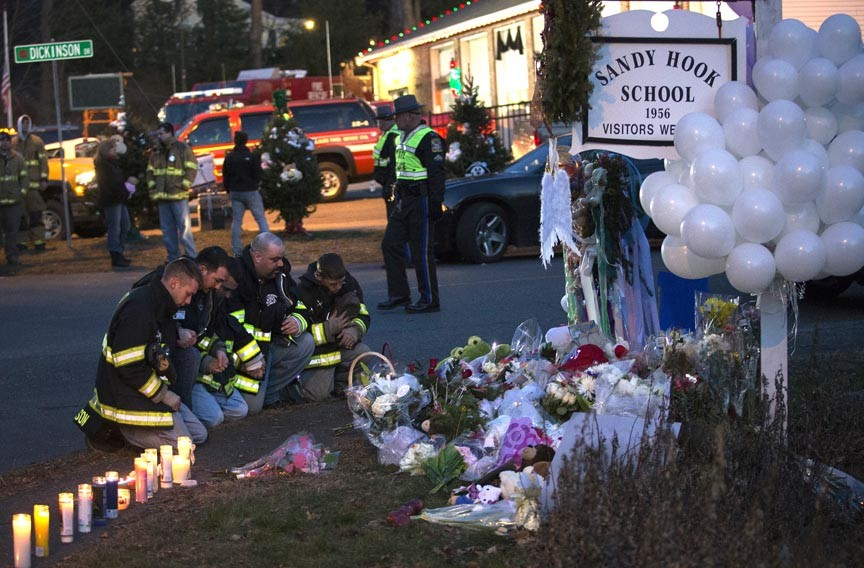 Firefighters kneel in front of a memorial along the road to Sandy Hook Elementary School, a day after the shooting in Newtown, Conn. - REUTERS/ADREES LATIF