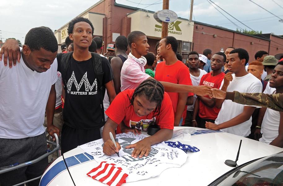 Garrick's friend, Danté Jackson, signs a T-shirt memorializing Garrick at his vigil. - SCOTT ELMQUIST
