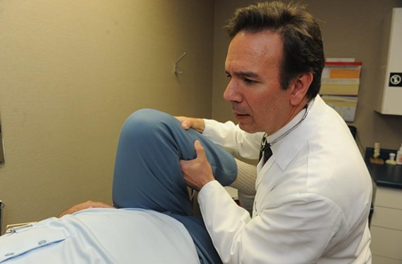 Gergoudis checks a retiree who slipped in the Caribbean surf and hurt his hip. - SCOTT ELMQUIST