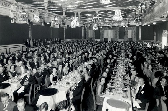 Guests pose for a group photograph at a December 1956 State Farm banquet in the hotel's Virginia Room. For many years the room was one of the state's largest convention spaces. - DEMENTI STUDIO