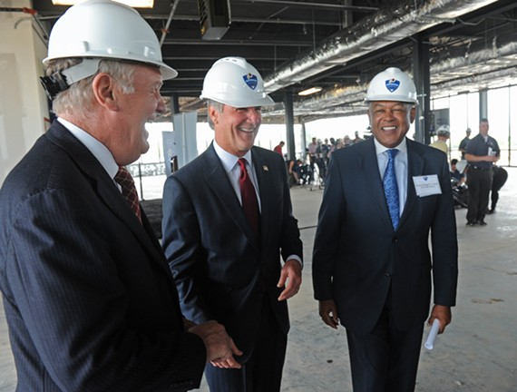 Hog happy: Bon Secours CEO Peter Bernard, Redskins General Manger Bruce Allan, and Richmond Mayor Dwight Jones share a moment in the nearly completed training center at the Redskins training camp. - SCOTT ELMQUIST