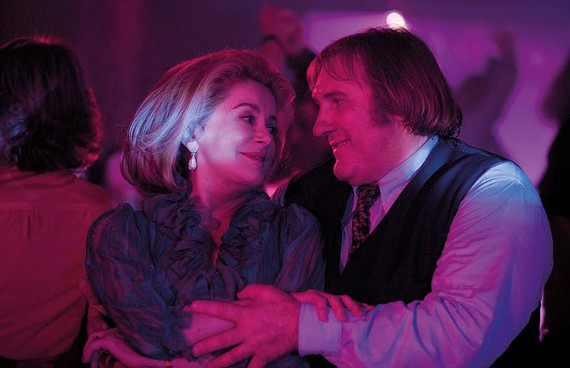 """I could lose myself in your chins."" Catherine Deneuve and Gerald Depardieu star in the strangely anachronistic French film, ""Potiche."""