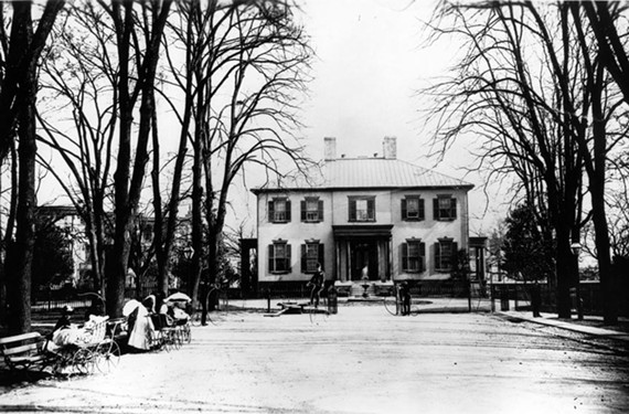 In this 1880s photograph the Executive Mansion serves as a backdrop for Capitol Square outings, including tending baby carriages and riding high-wheel bicycles when the neighborhood remained partially residential.