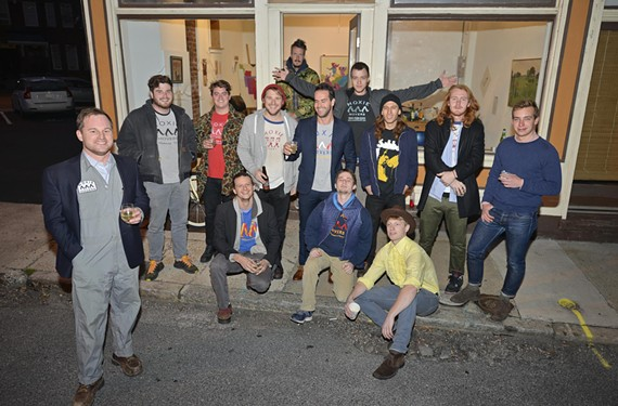 Jesse Whitacre, at left, celebrates with his artistically minded moving crew after a hard day of work at their gallery on Brook Road.