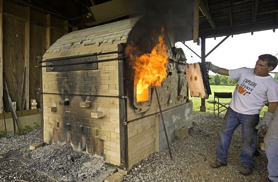 John Bryant opens the door to his wood-fired kiln that can get as hot as 2,400 degrees and bake hundreds of pots at a time.
