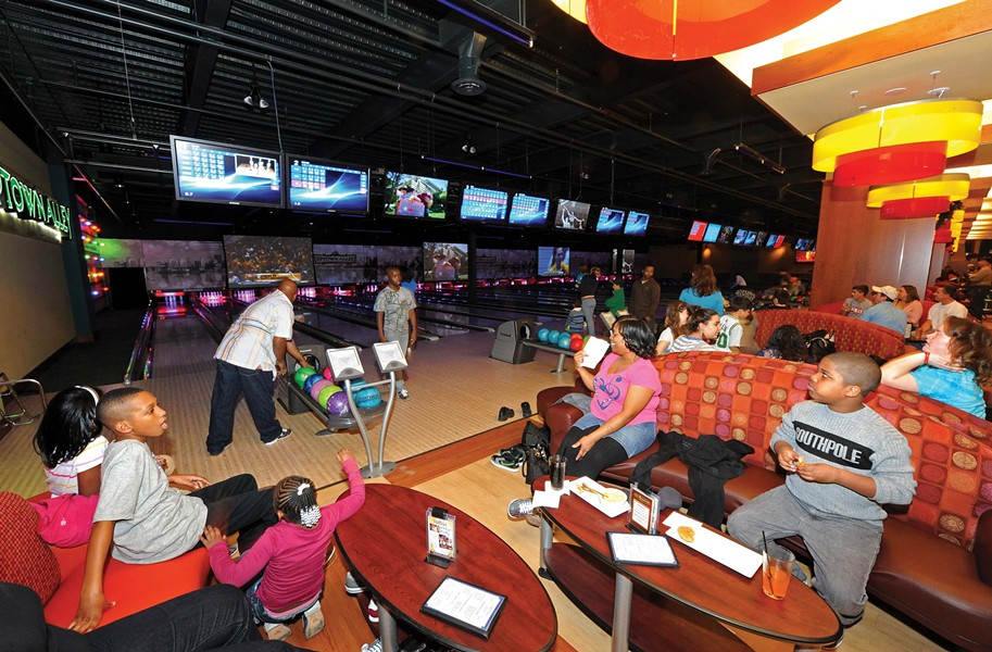 John Evans, left, reaches for a ball with his family at Uptown Alley in Midlothian. The 38-lane entertainment complex opened Dec. 6. - SCOTT ELMQUIST